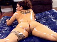 Tattooed ebony chick in oil jumps on big black cock for creampie